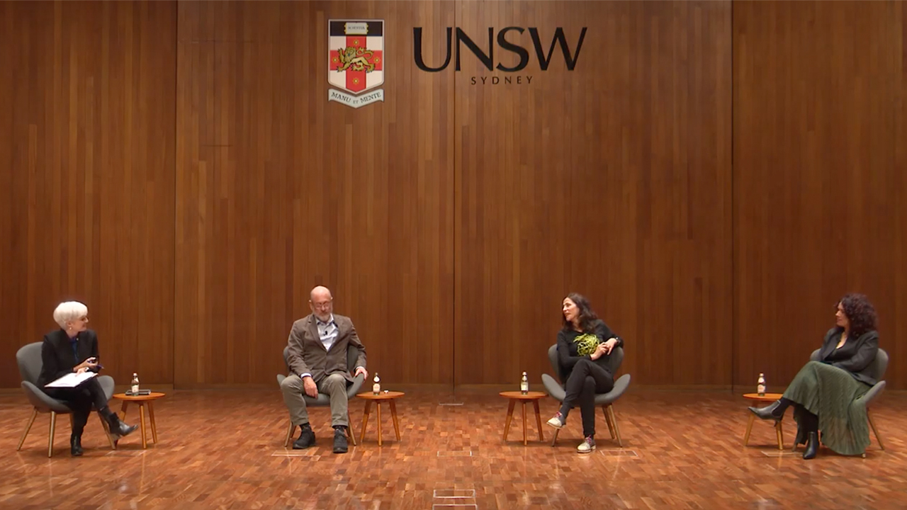 Panellists on stage underneath UNSW logo