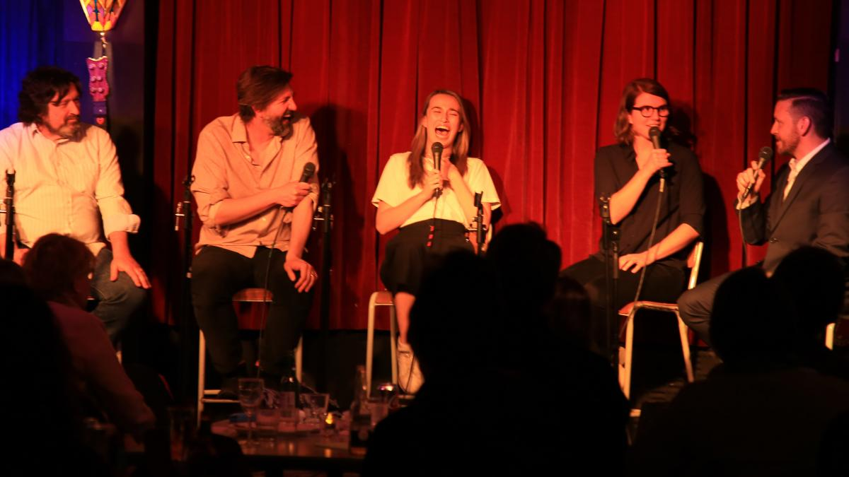 photo of people on stage laughing