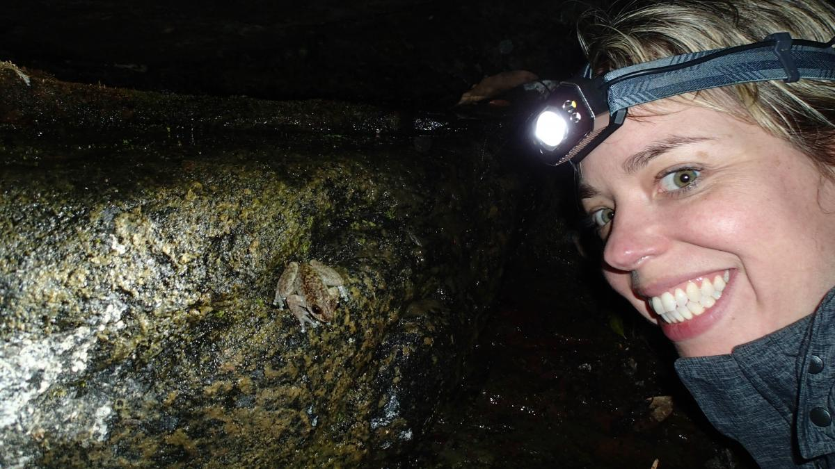 Photo of Jodi Rowly smiling near a small frog on a rock