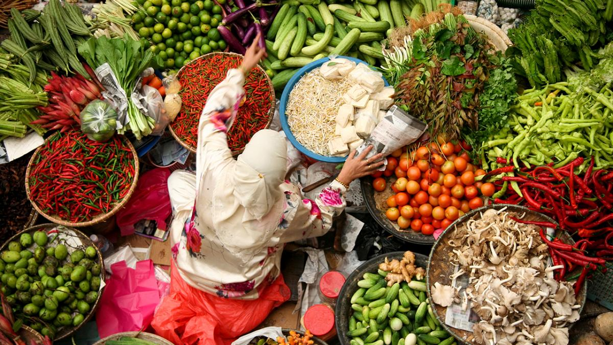 Woman amongst baskets of colourful food